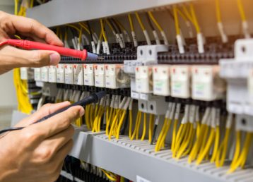 electricians-hands-testing-current-electric-control-panel_34936-1296