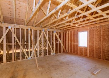 unfinished-attic-private-house-residential-construction-house-framing-agains_73110-7163