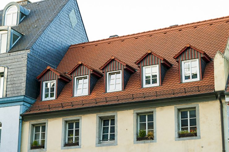 Roofs of old houses with roof windows and orange roof tiles in G